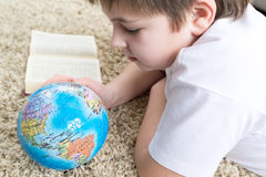 Boy studying the globe and reading  book Stock Photography