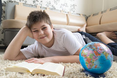 Boy studying the globe and reading  book Royalty Free Stock Photos