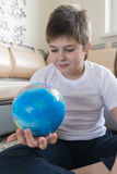 Boy studying globe in the room Stock Photo