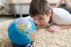 Boy studying globe in the room Stock Images