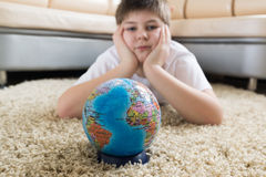 Boy studying globe in the room Stock Photography