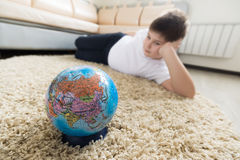 Boy studying globe in the room Royalty Free Stock Image
