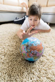 Boy studying globe in the room Royalty Free Stock Photography