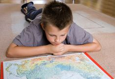 Boy studying a map. A young teenage boy lying on the carpet, studying a map Stock Photos