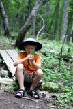 Boy studying nature. Young boy looking through magnifying glass at a leaf found on the hiking  trail Stock Photo