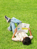 Boy studying outside. Boy lying down on grass outside and studying stock photos