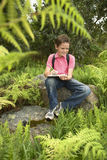 Boy Studying Plants And Writing On Clipboard. Happy young boy studying plants and writing on clipboard in forest Royalty Free Stock Photos