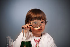 Boy studying. A substance in a test tube with a magnifying glass Stock Photography