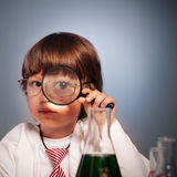 Boy studying. A substance in a test tube with a magnifying glass Stock Photo