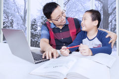 Boy studying and talking with dad at home Stock Photos