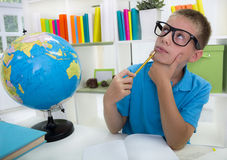 Boy studying about the world,and thinkig something Royalty Free Stock Image