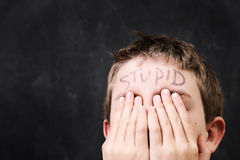 Boy with stupid written on his forehead. A close-up of a boy holding his eyes with the word `Stupid` written on his forehead royalty free stock photography