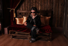 Boy in stylish clothes. Boy in a black leather jacket, jeans, baseball cap and sunglasses Royalty Free Stock Images