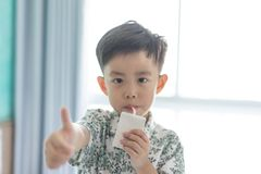 The boy is sucking milk from the milk box. He likes milk box so much stock image