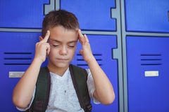 Boy suffering from headache against lockers. At school Stock Photos