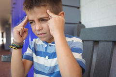 Boy suffering from headache while sitting on bench. At school Royalty Free Stock Photo