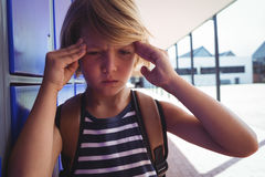 Boy suffering from headache while standing by lockers. In corridor at school Royalty Free Stock Photo