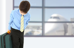 Boy in Suit at Airport. Young boy alone at airport with suitcase Stock Photo