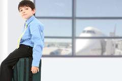 Boy in Suit at Airport. Adorable seven year old french american boy sitting on suitcase at airport Stock Image