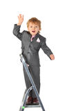 Boy in suit balances at step-ladder top Stock Photography