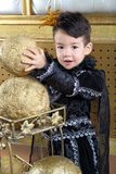 Boy in a suit of black prince raises ball Stock Photography