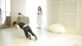 Boy in suit dancing break dance in front of a girl stock footage