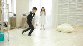 Boy in suit dancing break dance in front of a girl. Brother and sister at home, valentines day stock video footage