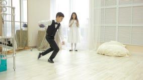Boy in suit dancing break dance in front of a girl stock video footage
