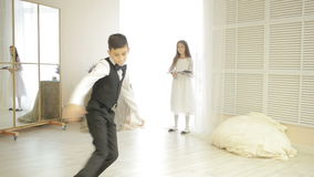 Boy in suit dancing break dance in front of a girl. Brother and sister at home, valentines day stock video