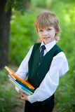 Boy in suit holding books in the park Stock Photo