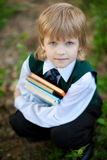 Boy in suit holding four books Stock Images