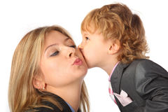 Boy in suit kisses mother Royalty Free Stock Photography