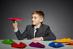 Boy in  suit launching color paper plane Royalty Free Stock Image