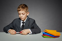 Boy in suit making color paper planes Stock Images