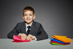 Boy in suit making red paper plane Stock Image