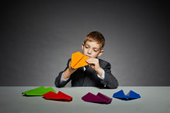 Boy in suit making yellow paper plane Stock Image