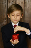 Boy in a suit with a red piggy bank Royalty Free Stock Photography
