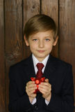 Boy in a suit with a red piggy bank Royalty Free Stock Photos