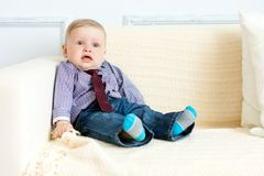 Boy in suit is sitting on sofa Stock Images