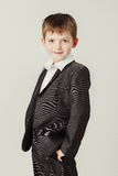 Boy in a suit smiles. Boy in a dark suit with his hands in his pockets Stock Photography