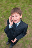 Boy in suit speaking over the mobile Royalty Free Stock Images