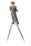 Boy in suit on step-ladder top Royalty Free Stock Photo