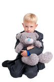 Boy in suit with teddy bear Stock Photo