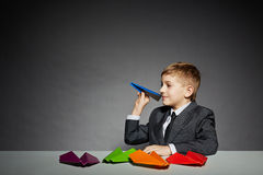 Boy in  suit about to launch color paper plane Stock Photos