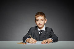 Boy in suit writing Royalty Free Stock Photo