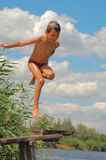 Boy Summer Fun Happy Diving. 7 years old boy jumping into water on the cloudy sky background royalty free stock image