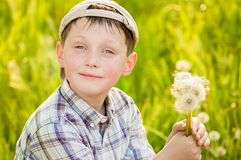 Boy on summer nature with dandelions Royalty Free Stock Photography