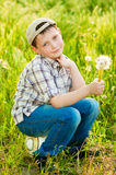 Boy on summer nature with dandelions Royalty Free Stock Image