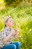 Boy on summer nature with dandelions Stock Photo