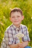 Boy on summer nature with dandelions Stock Images